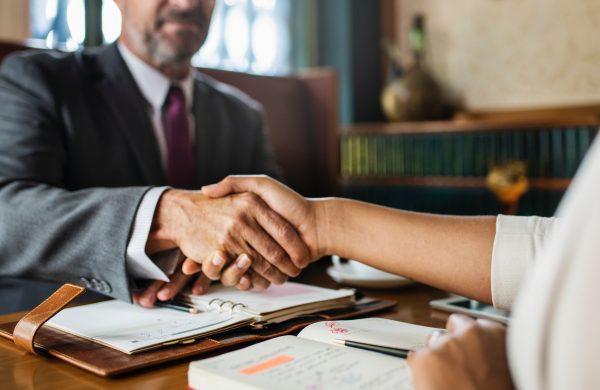 мъж и жена си стискат ръцете в офис обстановка