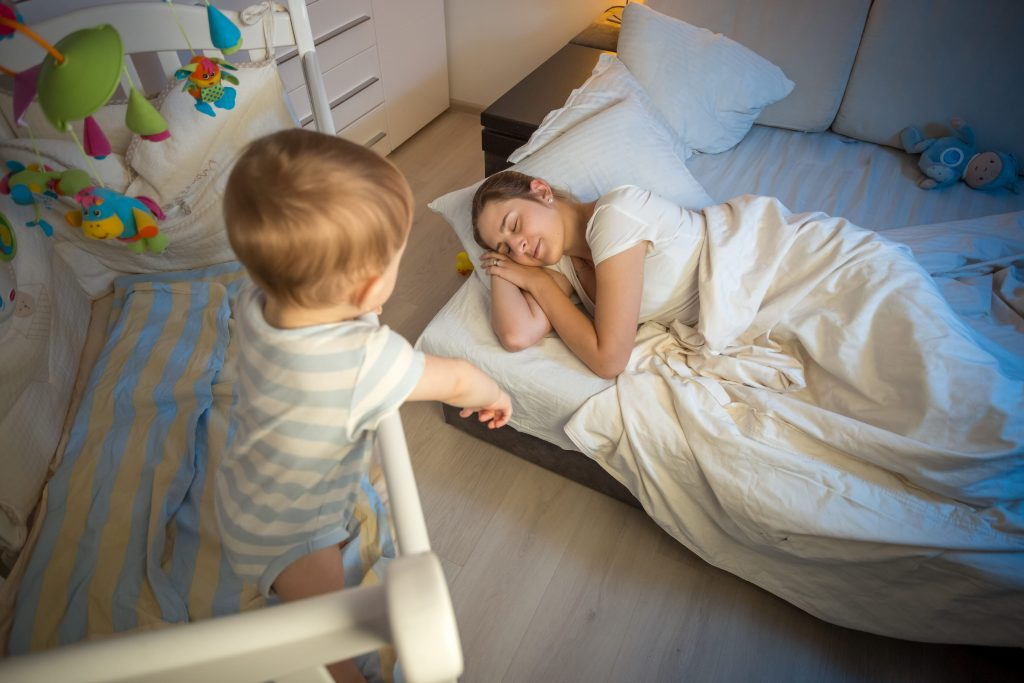 дете в кошарка гледа майка си спяща на земята
