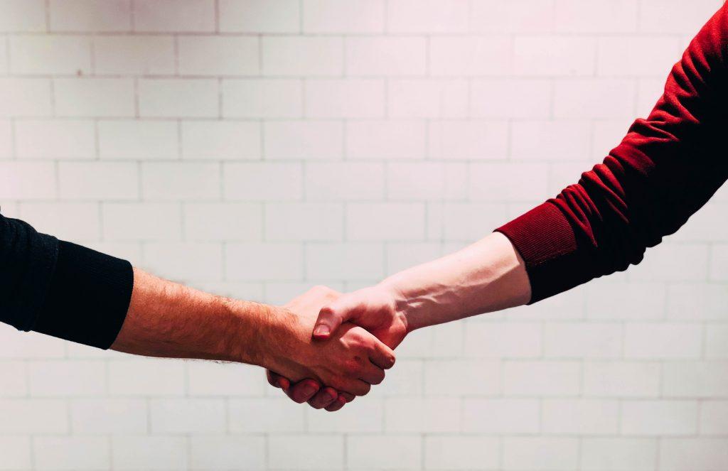 двама мъже си стискат ръцете при предсварителен договор за покупка