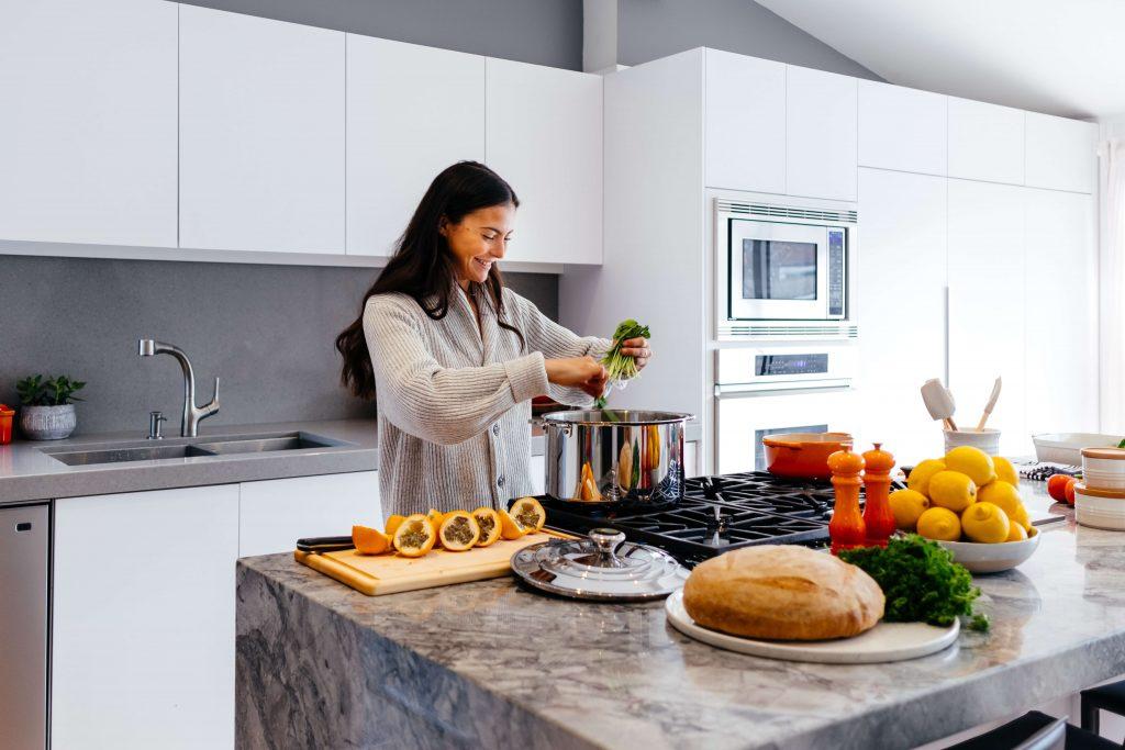 млада жена готви в просторна кухня