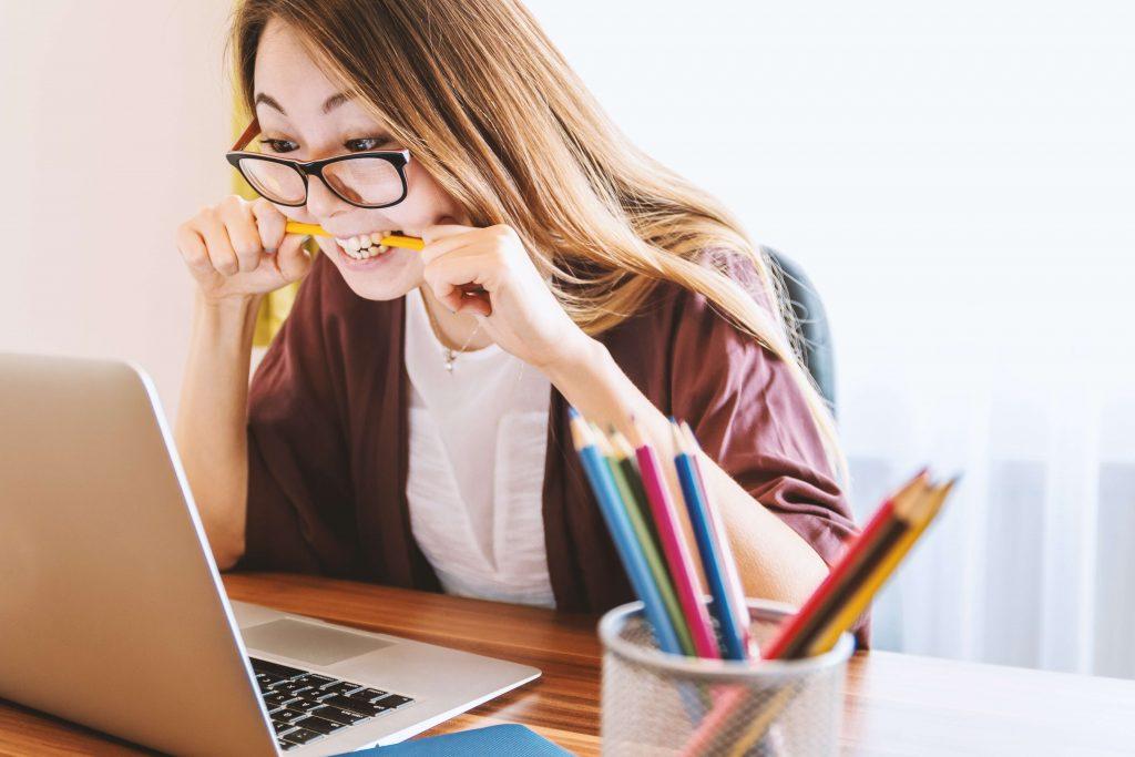 момиче хапе нервно молив пред компютъра