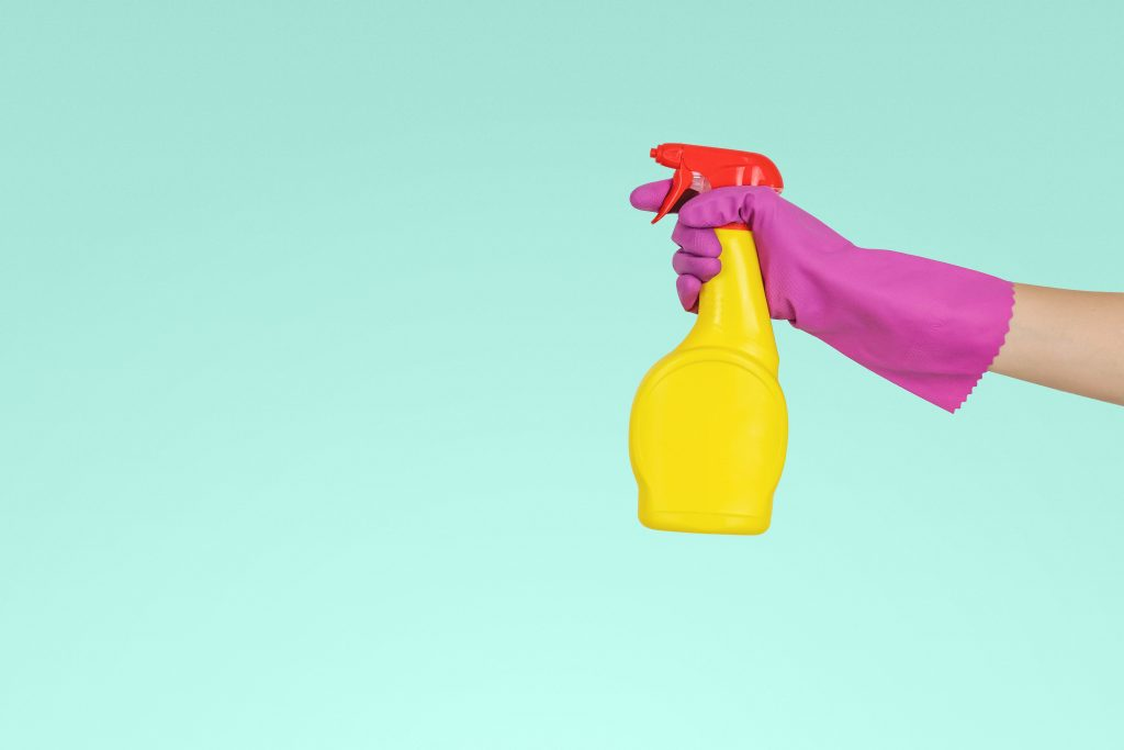 ръка с гумена ръкавица държи почистващ препарат-спрей