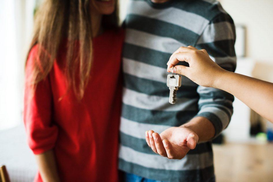 брокер подава ключове на млада двойка след покупка на апартамент