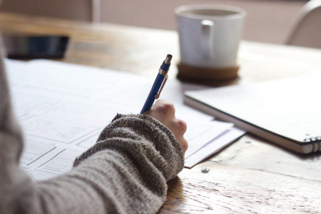 момиче пише с химикал върху бюро с разхвърлени документи