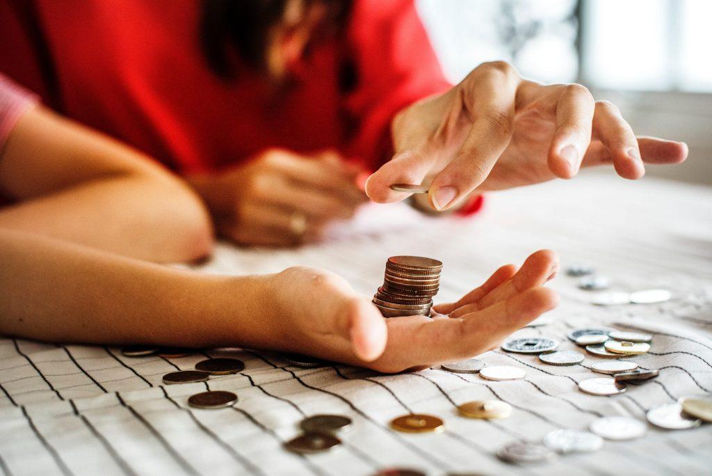жена пуска стотинки върху мъжка ръка