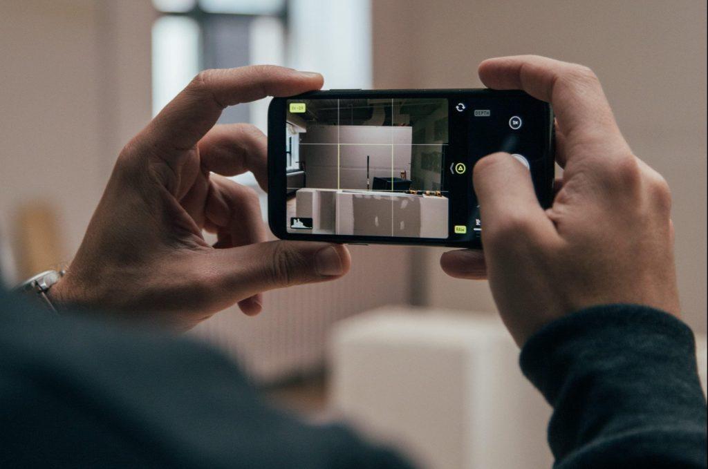 мъж държи телефон и снимка в апартамент