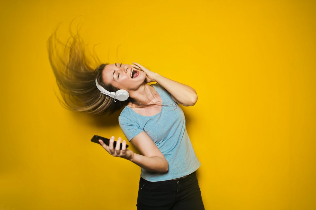русо момиче слуша музика и танцува на фона на жълта стена