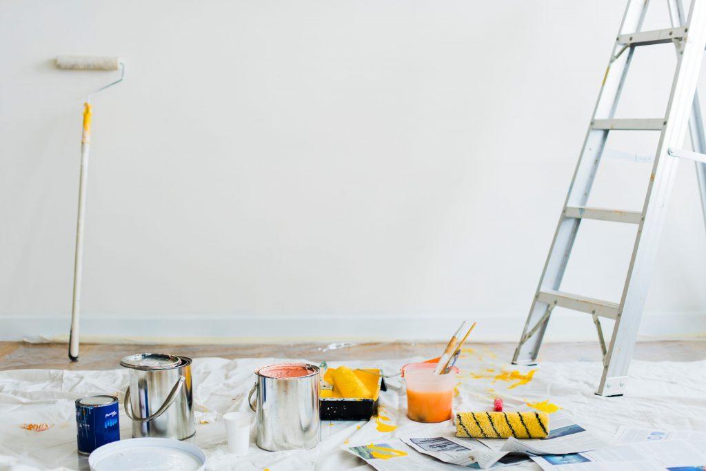 стълба, кофи с боя и мече за боядисване на фона на бяла стена
