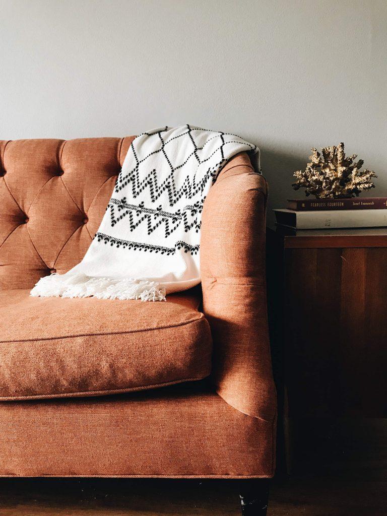 диван с наметнато одеало до шкаф, декориран с книги