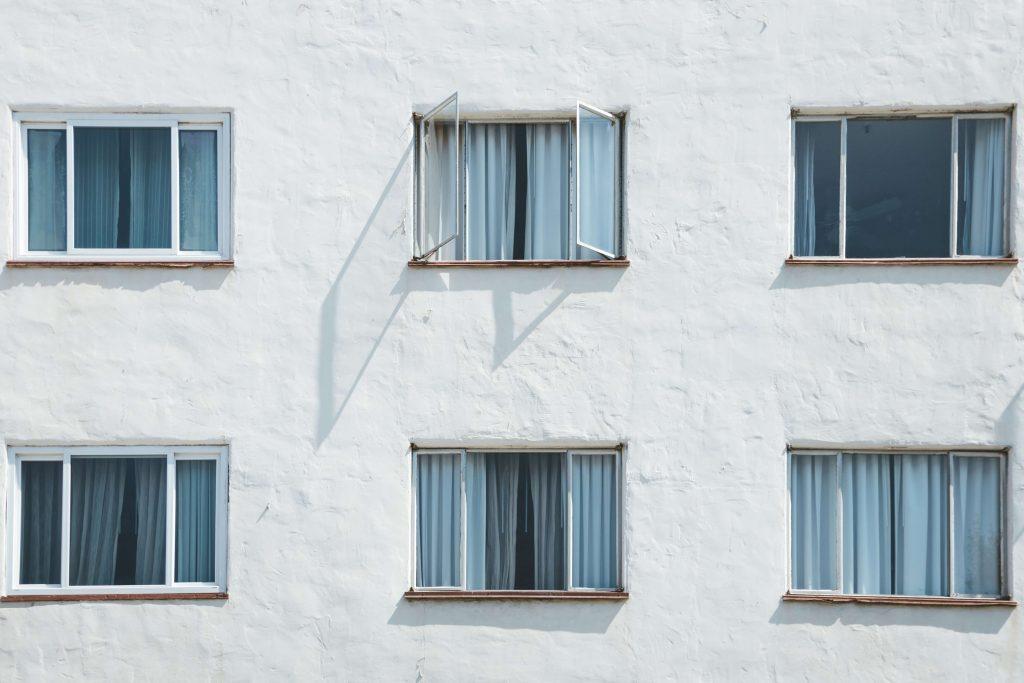 отворени прозорци със сини пердета