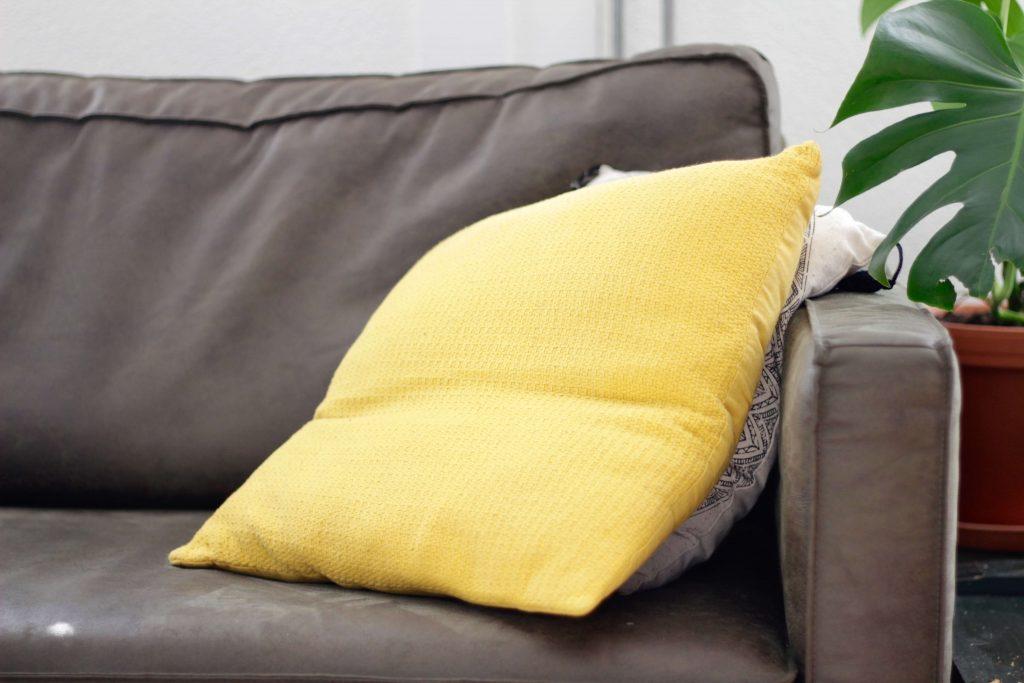 жълта възглавница върху кафяв диван