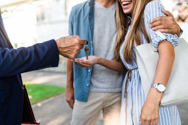брокер подава ключове на млада двойка