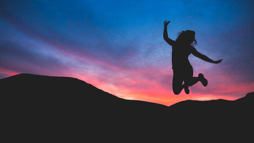 Момиче скача във въздуха на фона на красив залез