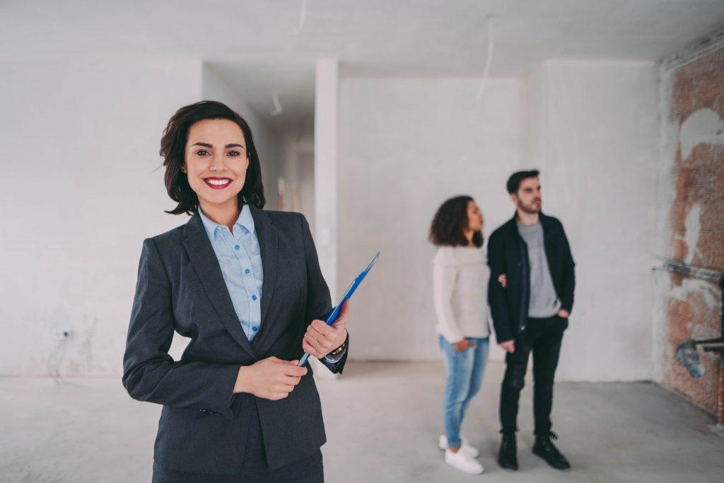брокер на недвижимо имущество показва имот на двойка купувачи