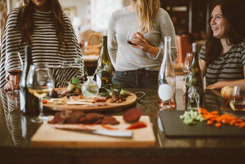 жени около маса с питиета и храна