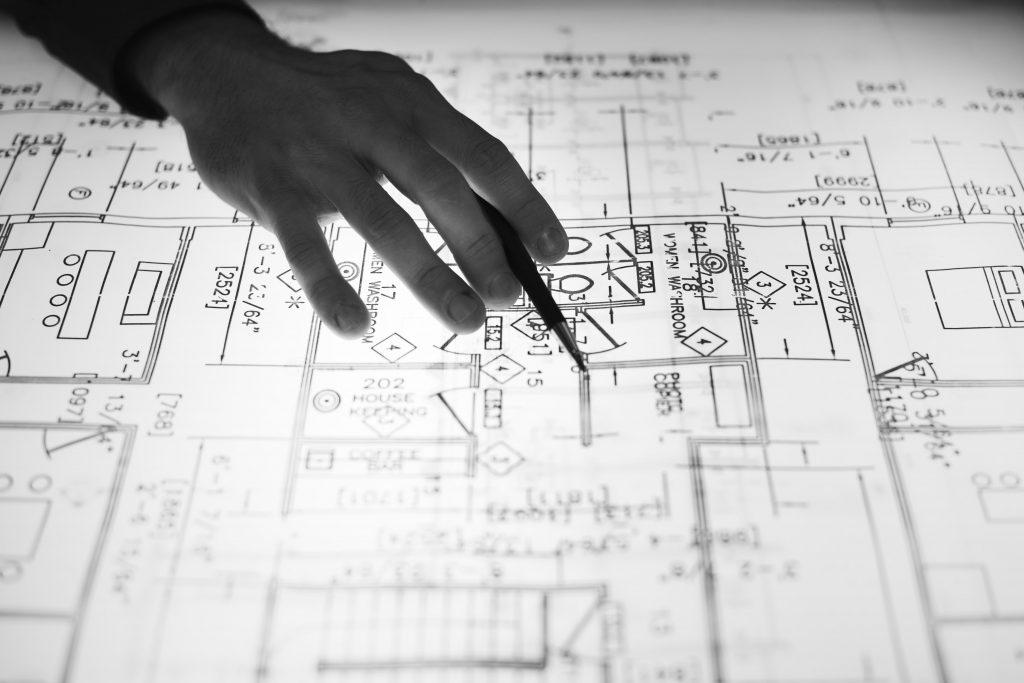 ръка върху скица с разпределение на жилище
