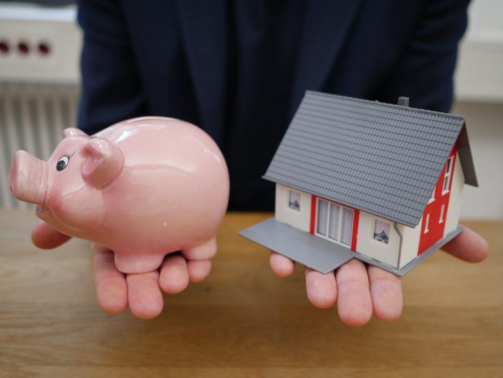 мъж държи касичка-прасе и макет на къща