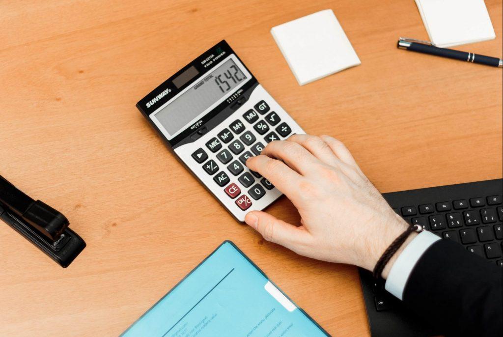 мъж използва калкулатор на дървено бюро