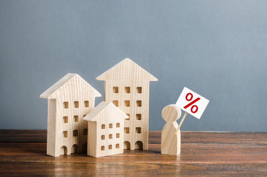 фигура държи знак % на фона на жилищни сгради