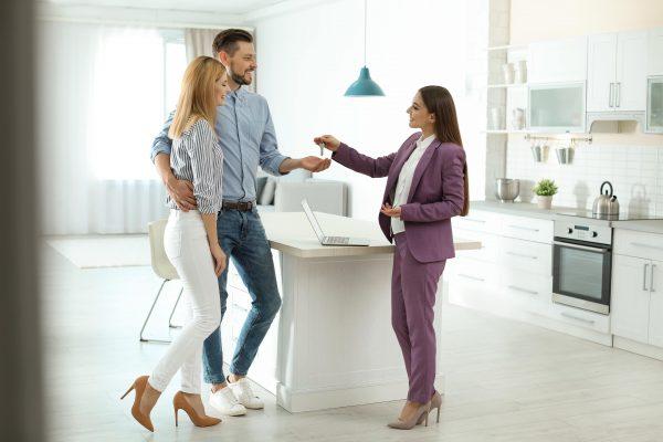 Брокер подава ключове на двойка след успешна покупка на апартамент