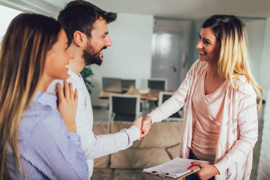 Брокер и двойка си стискат ръцете при продажба на апартамент