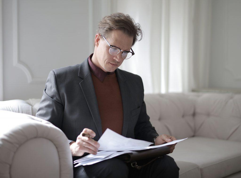 мъж чете документи задълбочено