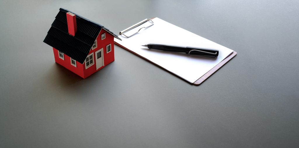 макет на къща, документ и химикалка