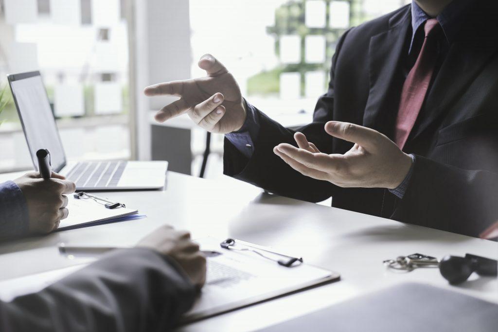двама мъже в костюми разговарят седнали на бюро