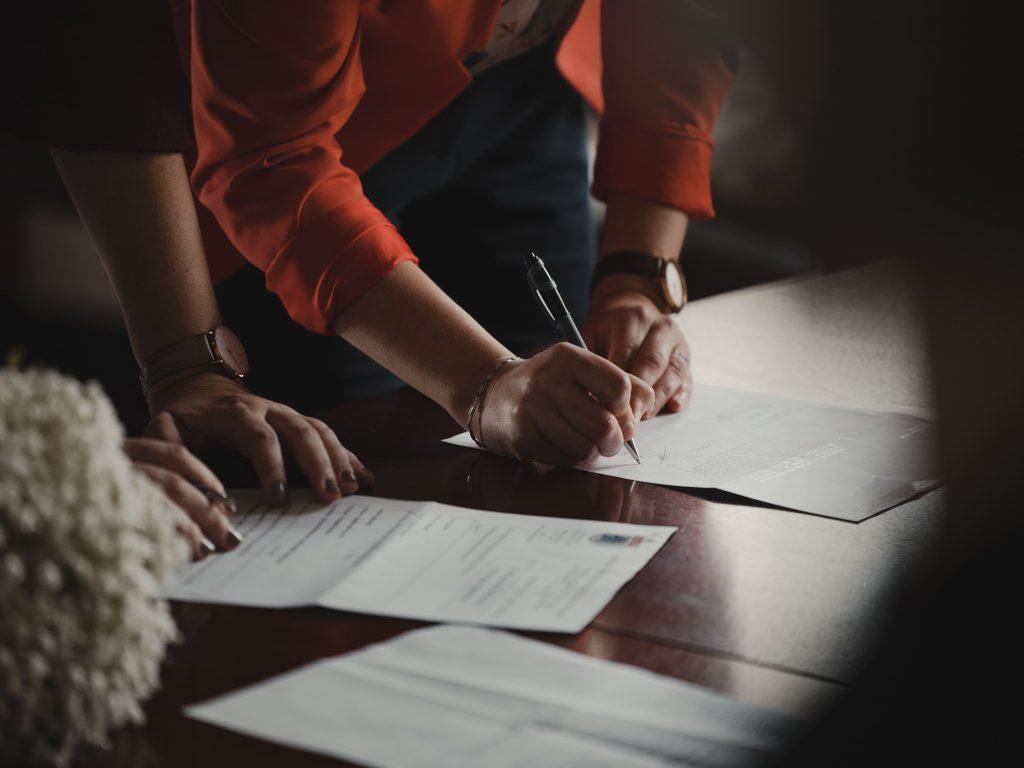 мъж и жена подписват документи за собственсот на апартамент на зелено