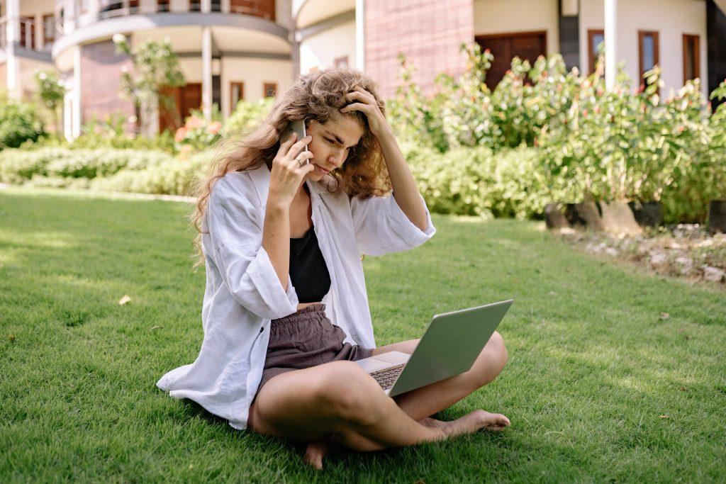 момчие се държи за главата докато говори по телефона и гледа в лаптопа си