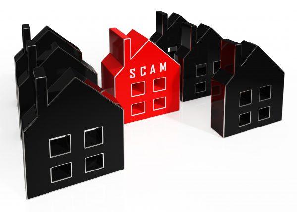 """Макети на няколко черни къщички и една червена с надпис """"измама"""""""