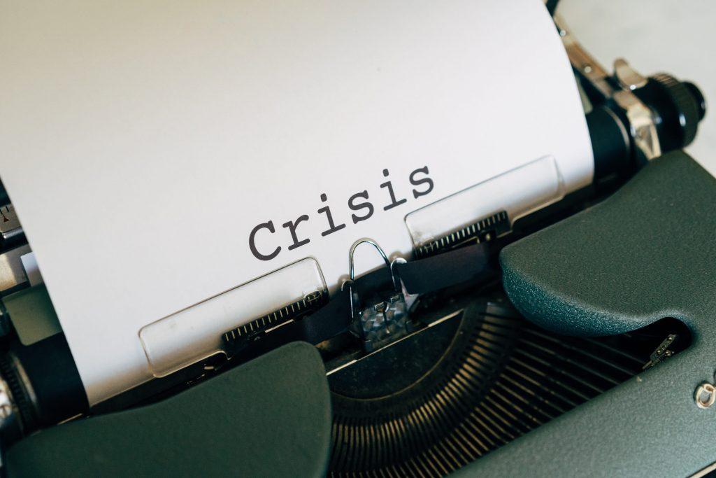 """печатна машина, от която стърчи бял лист с надпис """"Криза"""""""