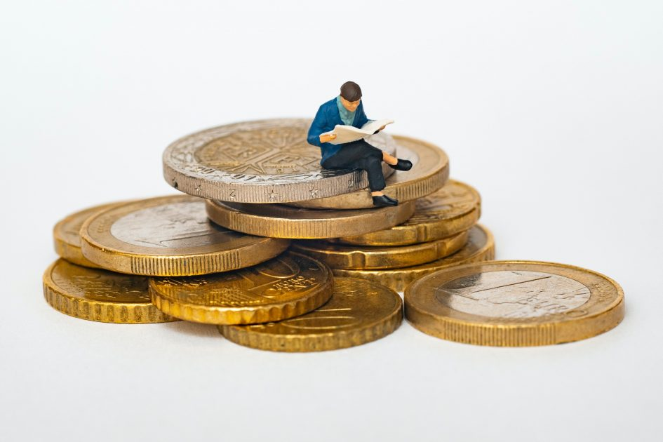 фигура на мъж седи върху купчина от монети