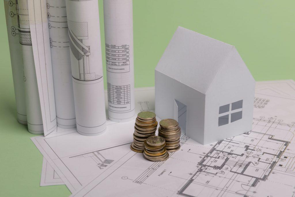 купчина от монети на фона на чертежи и макети на къщи