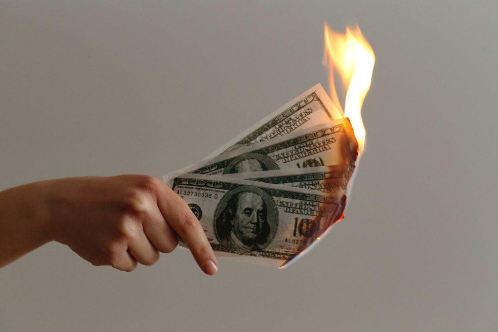 ръка държи банкноти, които горят